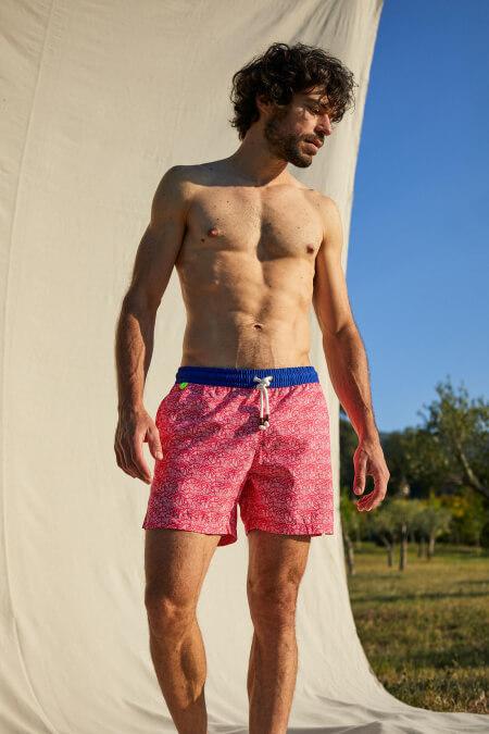 Man wearing a Fushia Tropics swimsuit with elasticated belt