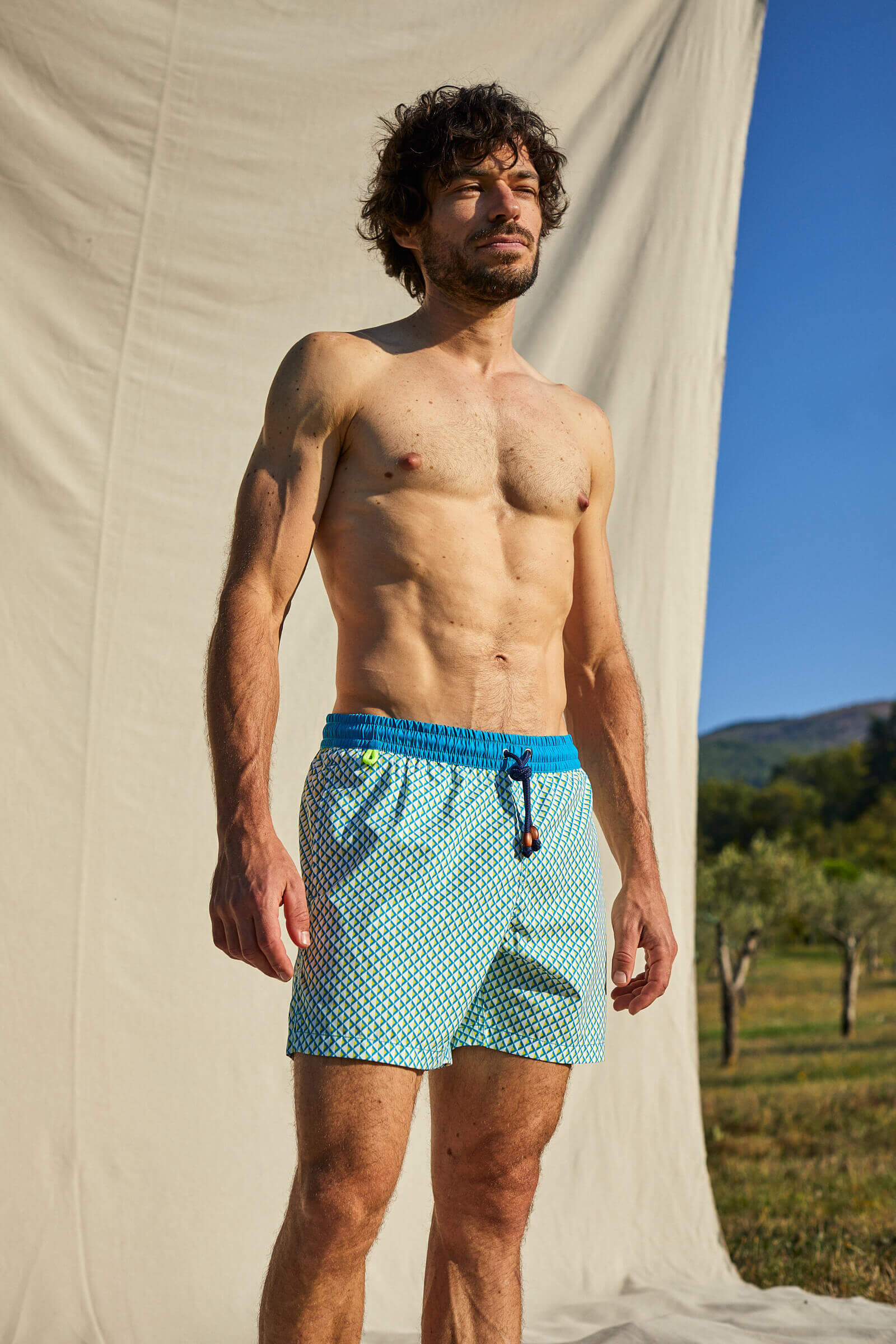 Man wearing a Turquoise Miami Beach  swimsuit with elasticated belt